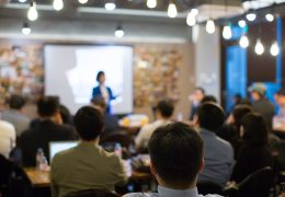 Audience Watching a Presentation. Defocused Blurred Presenter During Conference Meeting